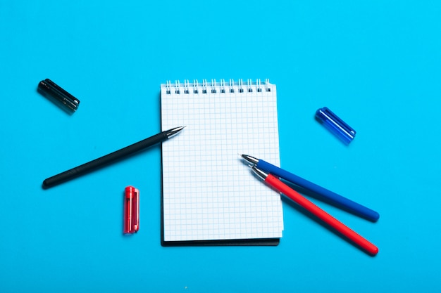 ノートブック、ペンと青色の背景にトップビューワークスペースモックアップ