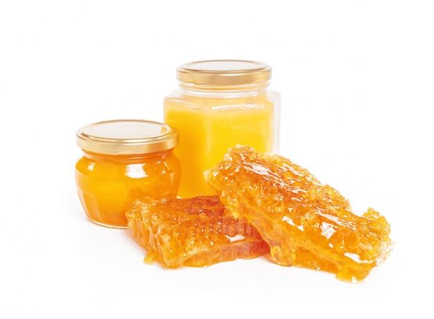 蜂蜜と白い背景で隔離の棒の瓶