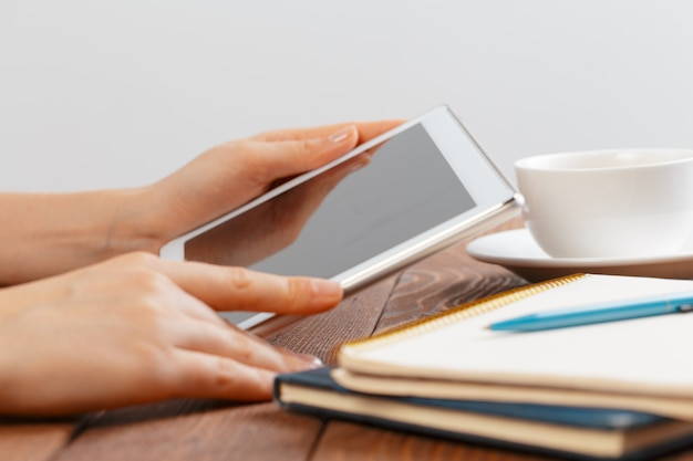 木製のワークスペーステーブルの上に空白のタブレットデバイスを保持している女性