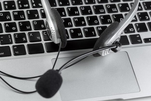 コールセンターサポートのコンセプト。キーボードコンピューターのラップトップ上のヘッドセット