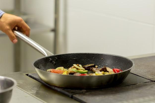 キッチンで火でガスコンロで野菜を揚げるシェフ