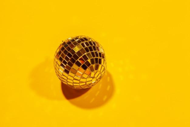 色の背景上の日の光で輝く光沢のあるパーティーディスコボール