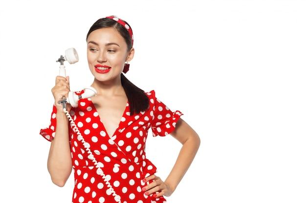 ピンナップスタイルに身を包んだ携帯電話と美しい若い女性の肖像画。