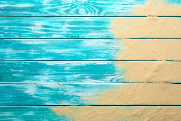 Морской песок на синем деревянном полу, вид сверху с копией пространства