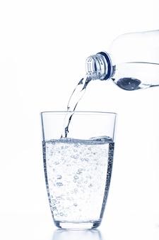 Вода льется в стакан на белом фоне