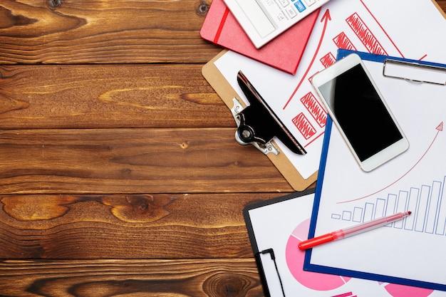 Вид сверху деловой бумаги диаграммы или графика на деревянный стол