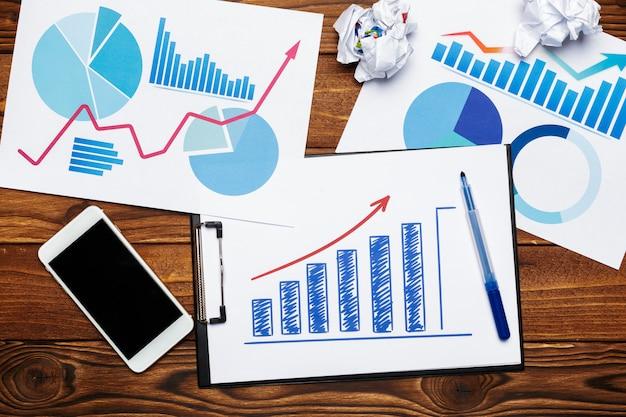 木製のテーブルにビジネス紙チャートまたはグラフのトップビュー