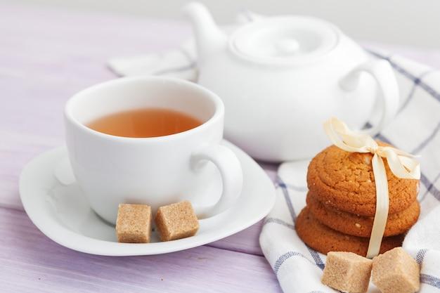 ライラックの木製の背景上のクッキーとお茶のカップ