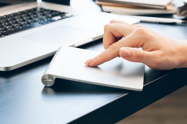 ラップトップコンピューターのマウスパッドに触れる女性の手のクローズアップ
