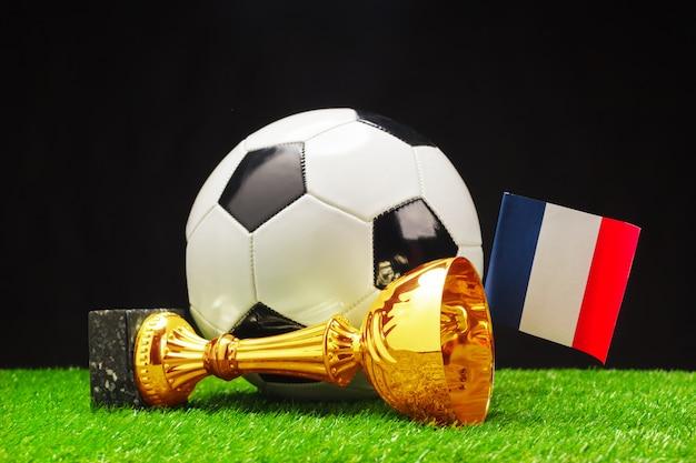 Футбольный кубок с футбольным мячом на траве