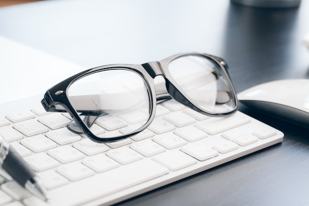 Очки на ноутбуке с ручкой, крупным планом