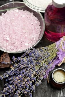 暗いテーブルの上にラベンダー、ハーブ、化粧品、塩の芳香組成