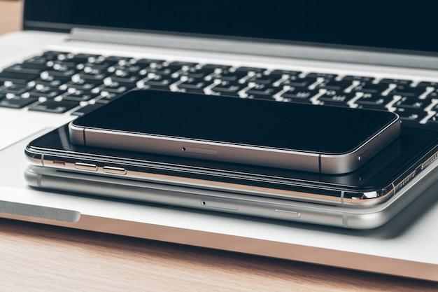 テーブルの上のノートパソコンと携帯電話。ワークスペース。