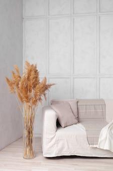 Гостиная в скандинавском стиле с тканевым диваном, подушками, пледом и растением в вазе на сером фоне стены
