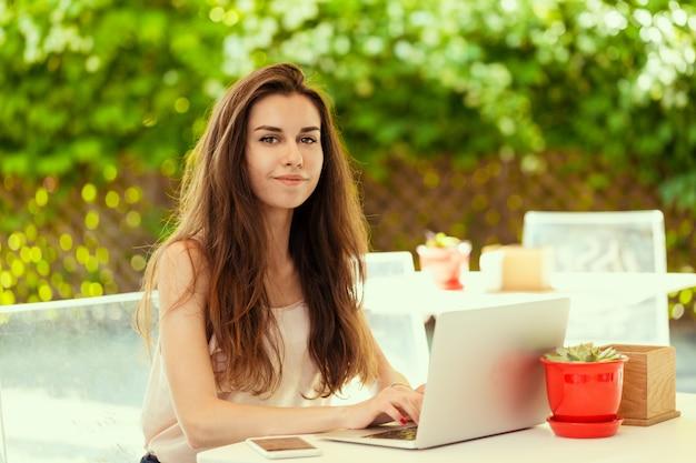 コーヒーブレークを持つラップトップでカフェで美しい魅力的な女性