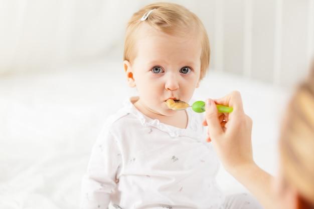 Маленький ребенок кормит ложкой