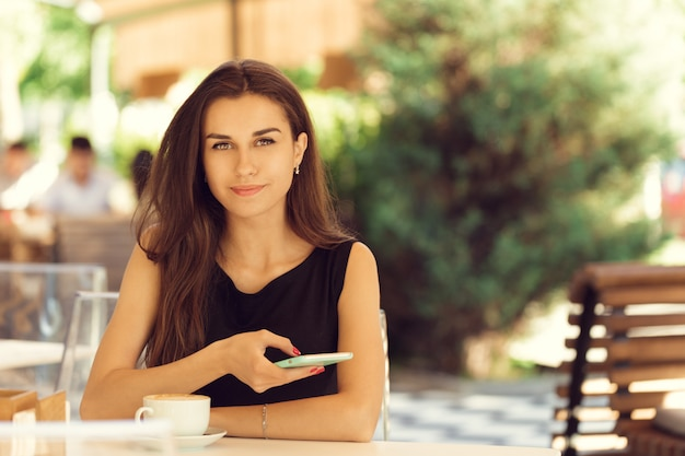 カフェで携帯電話を使用して女性