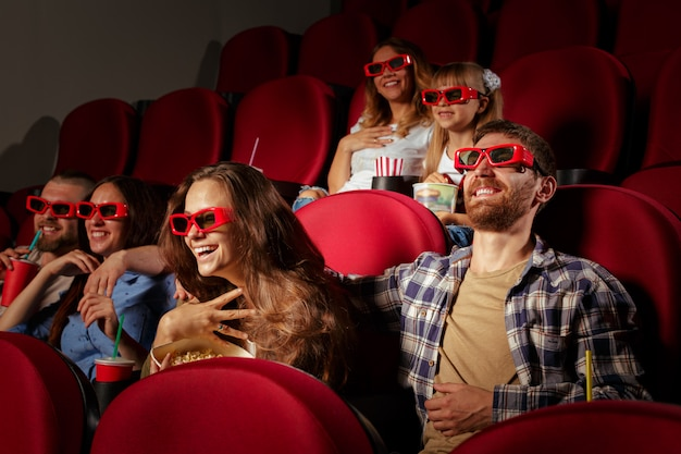 ポップコーンとドリンクの映画館に座っている友人のグループ