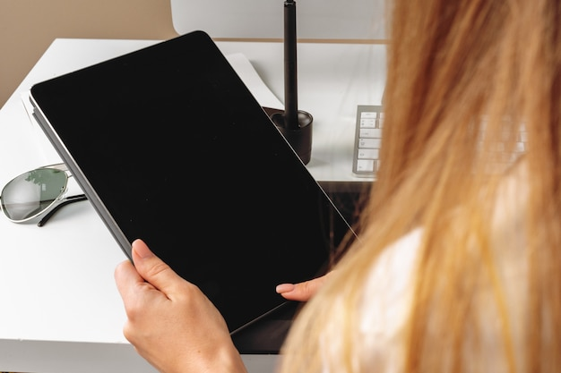 オフィスのテーブルに座ってデジタルタブレットを使用して女性