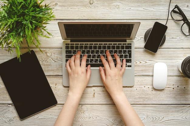 女性の手、ノートパソコンの上面とフラットレイアウトオフィスデスクワークスペース