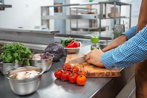 レストランのキッチンで調理する茶色のエプロンのシェフ