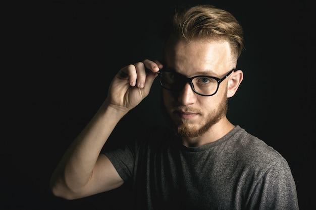 黒の背景の上の若い男の肖像