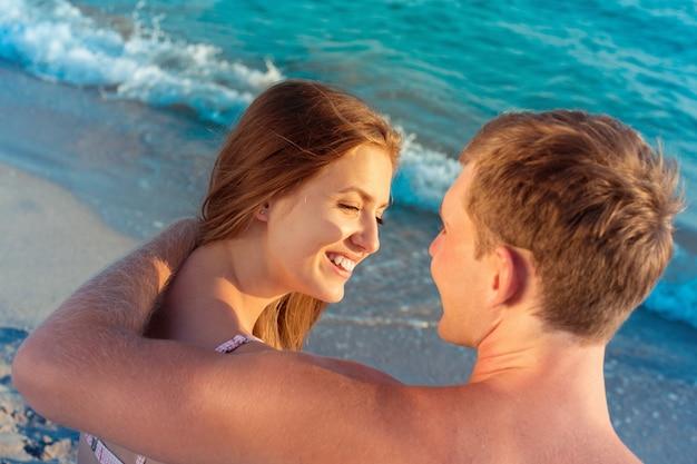 ビーチで楽しんで美しい愛情のあるカップルの肖像画