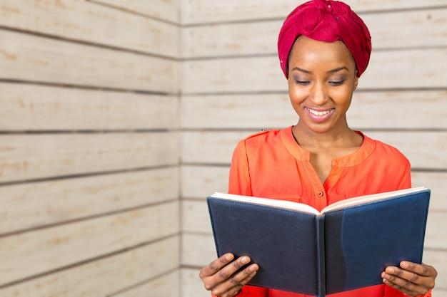本を保持している美しいアフロアメリカンの女性