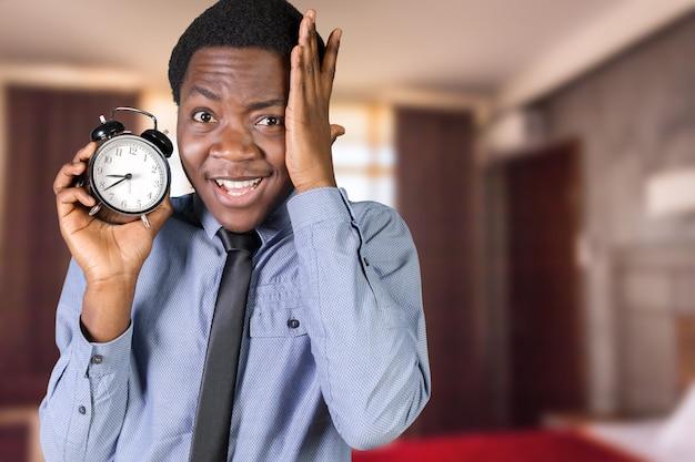 Молодой черный человек с будильником