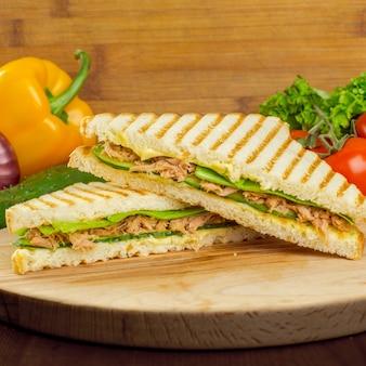 木製の背景にサンドイッチ