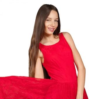 Красивая девушка с длинными каштановыми волосами в красном платье