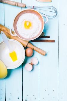 生地の準備。生地の材料-卵と小麦粉を麺棒で。木製の上。
