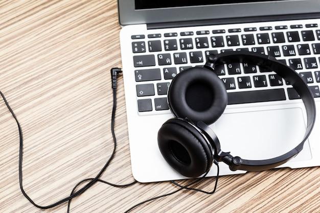 テーブルの上のノートパソコンとヘッドフォンをクローズアップ