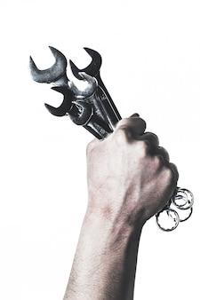 メカニックの手が白で隔離の手でスパナツールを保持します。