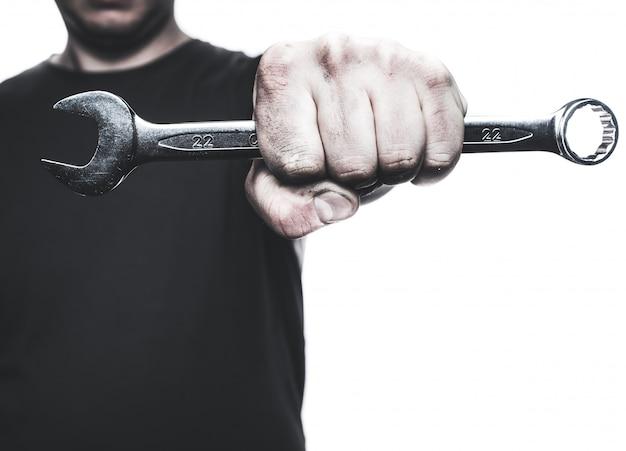 Инструмент гаечного ключа руки механика в руке изолированный на белизне