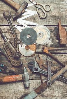Беспорядок старинных столярных инструментов на старых деревянных фоне