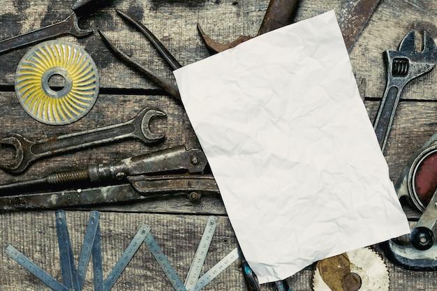 ヴィンテージさびたツールに囲まれたコピースペースを持つ紙のトップビューシート