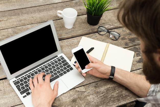 オフィスで彼のスマートフォンで流行に敏感な男のテキストメッセージのクローズアップ