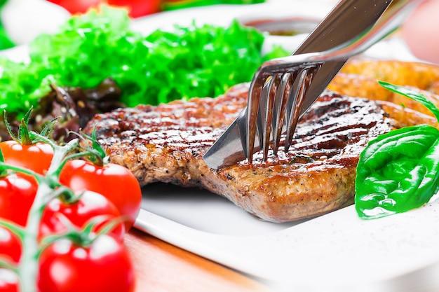 ポテトウェッジと牛肉のグリルステーキをクローズアップ
