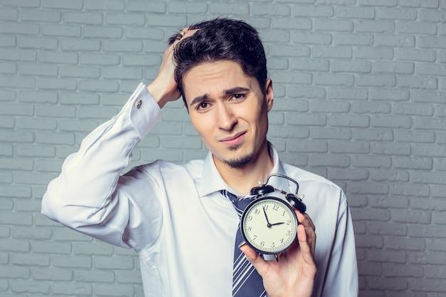 手に目覚まし時計を持ったビジネスマン