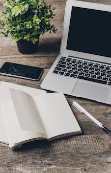ノートパソコンと消耗品のオフィスデスクをクローズアップ