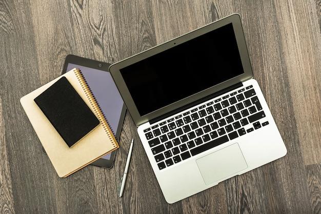 暗い木製のテーブル、オフィスインテリアのラップトップのクローズアップ