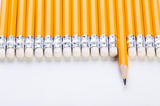 Ряд желтых карандашей с одним торчащим на белой стене, бизнес и концепция лидерства