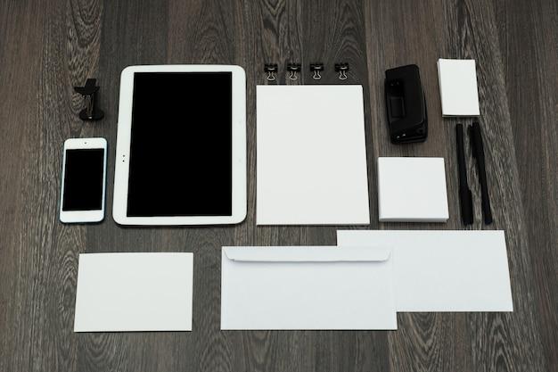 木製の壁にタブレットとブランド要素のモックアップを設計する