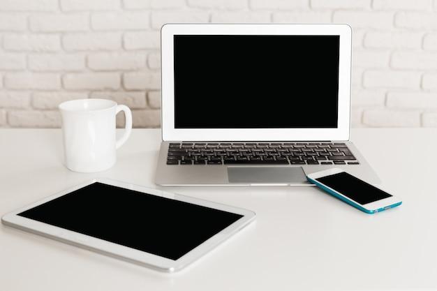 Набор современных компьютерных устройств с ноутбуком, цифровой планшет и смартфон крупным планом на белом столе