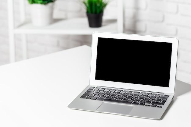 照明付きの白い部屋、家やオフィスのインテリアのラップトップ