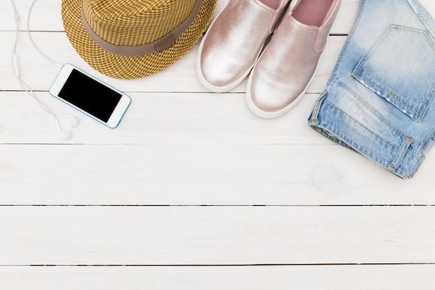 木の床にデニムのショートパンツ、麦わら帽子、靴