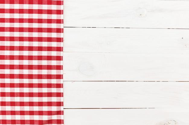 白い木製のテーブルに赤い市松模様のキッチンタオル