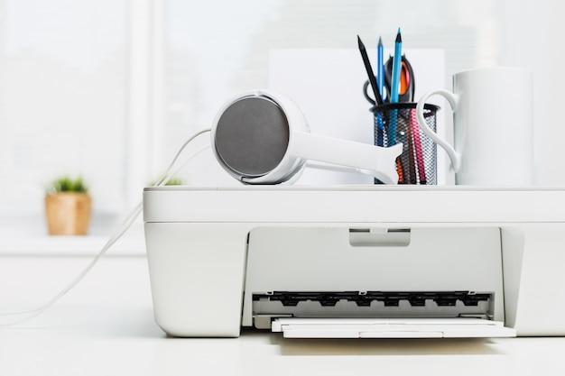 白いホームプリンターとオフィスのテーブルに白いヘッドフォン
