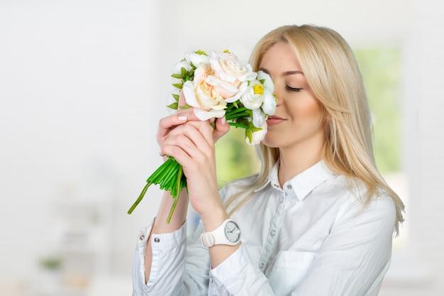 花を持つ美しい若い女性